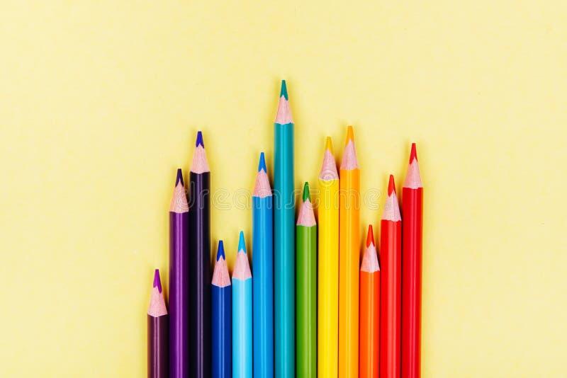El color dibujó a lápiz en fila en fondo amarillo foto de archivo
