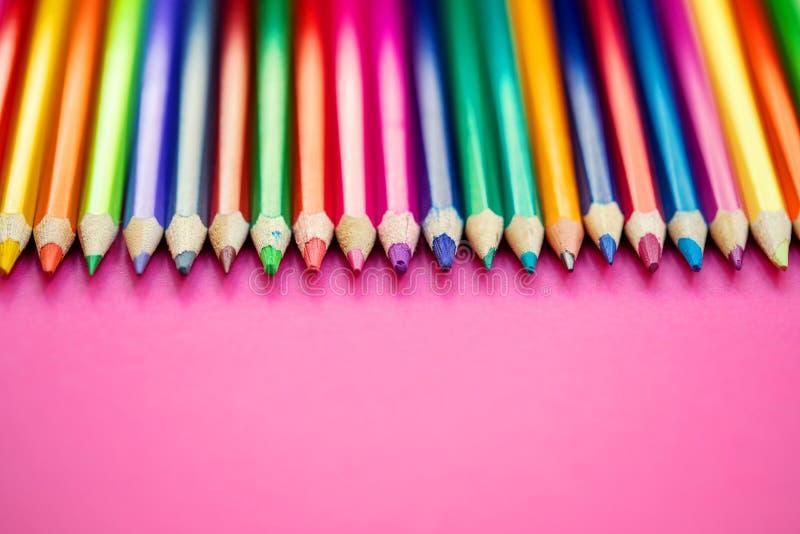 El color dibujó a lápiz en fila en fondo rosado Educación, escuela imágenes de archivo libres de regalías