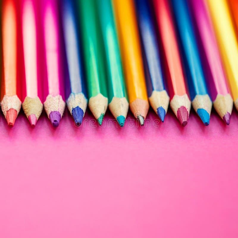 El color dibujó a lápiz en fila en fondo rosado Educación, escuela foto de archivo libre de regalías