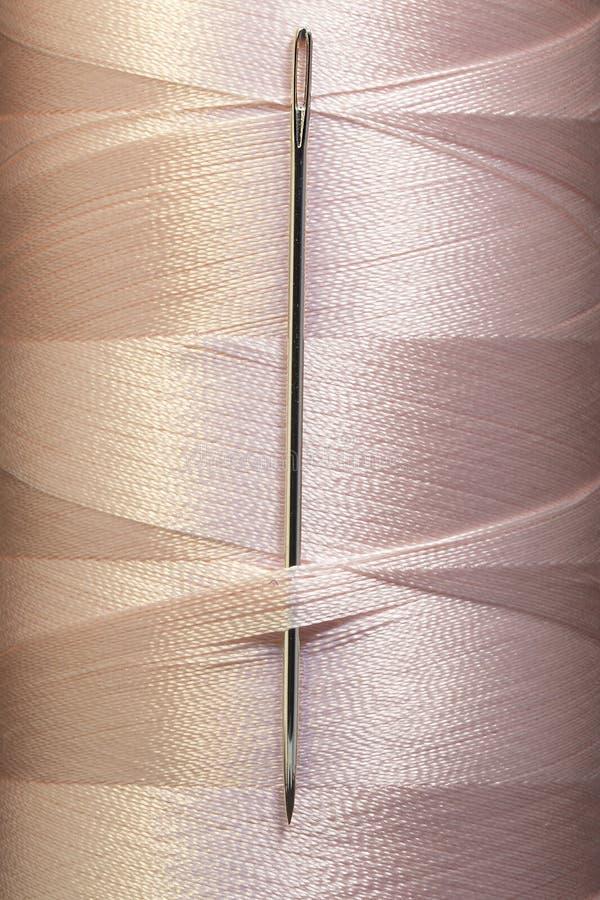 El color rosado rosca en carrete con la aguja de costura, macro fotografía de archivo libre de regalías