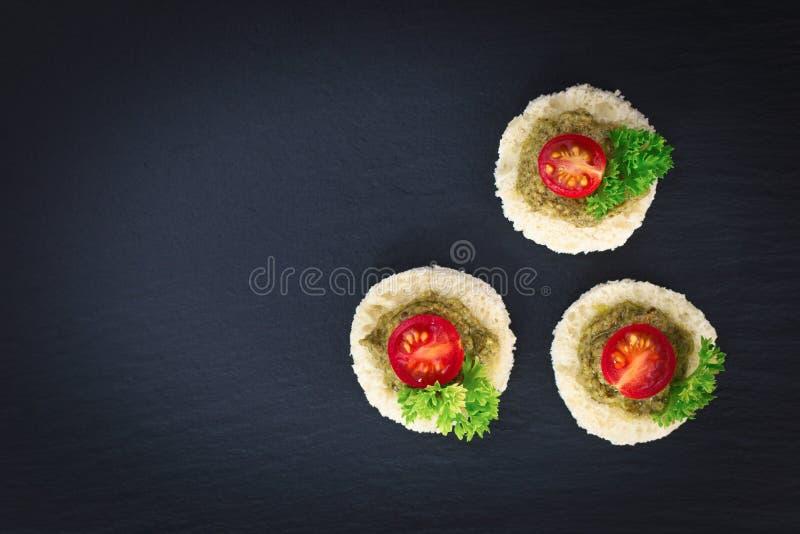 El comida para comer con los dedos para la salsa hecha en casa del pesto del Canape del partido en el tomate superior y el pereji imágenes de archivo libres de regalías