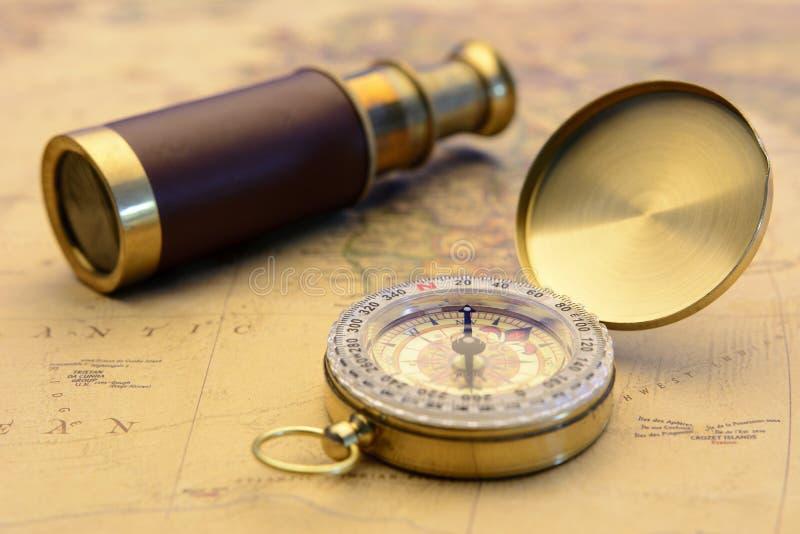 El compás de cobre amarillo y el telescopio viejo en vintage trazan concepto del explorador del mundo fotografía de archivo libre de regalías