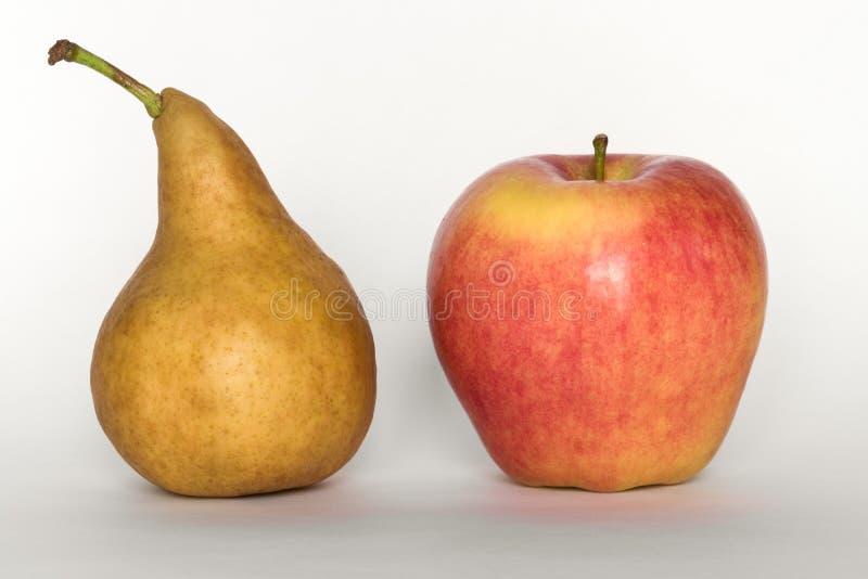 El comparar y manzana y una pera imagen de archivo