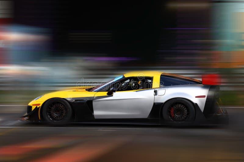 El competir con de coche de carreras amarillo y blanco en pista de la velocidad imagen de archivo libre de regalías