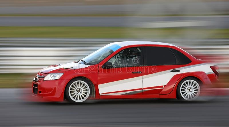 El competir con de coche de carreras rojo en circuito de carreras fotografía de archivo