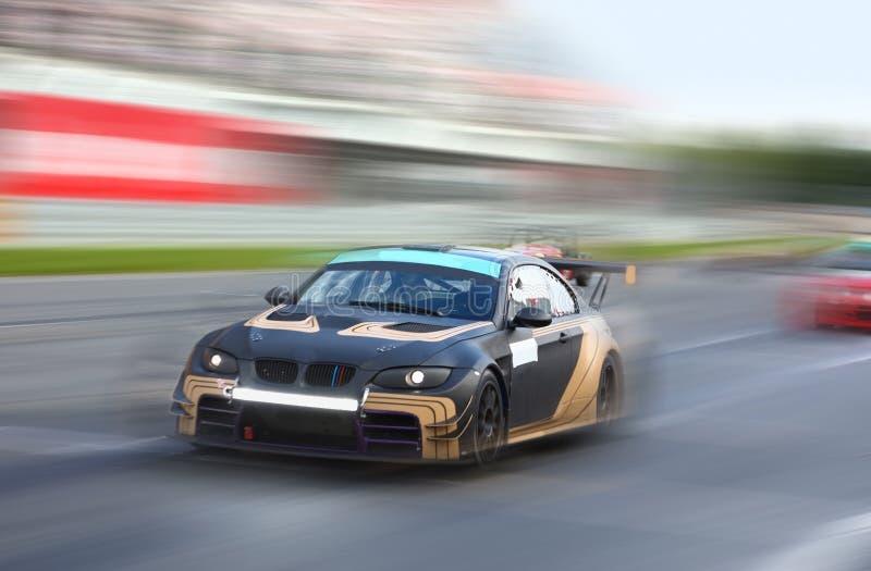 El competir con de coches de carreras en la velocidad en una pista que compite con imagen de archivo