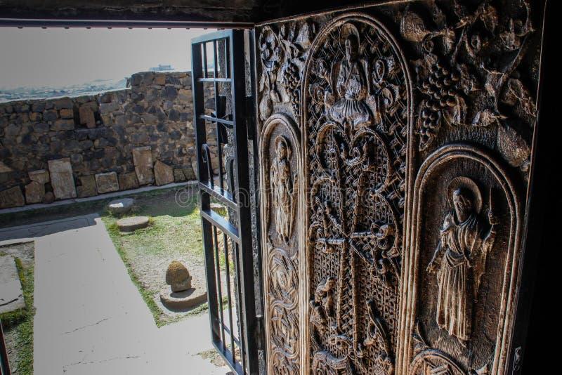 El complejo del templo de un monasterio cristiano antiguo y de puertas decorativas con los bajorrelieves que representan a santos foto de archivo