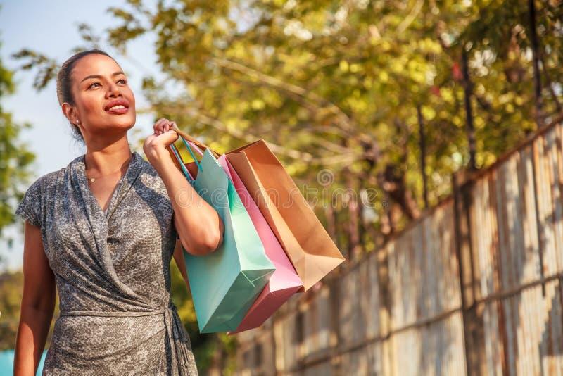 El comprador asiático de la mujer es que hace compras y que sostiene los panieres coloridos que miran de lado a la izquierda el e imagen de archivo libre de regalías