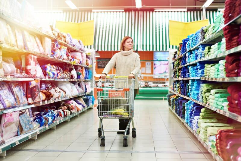 El comprador de la mujer con el producto de la carretilla elige productos en tienda fotos de archivo