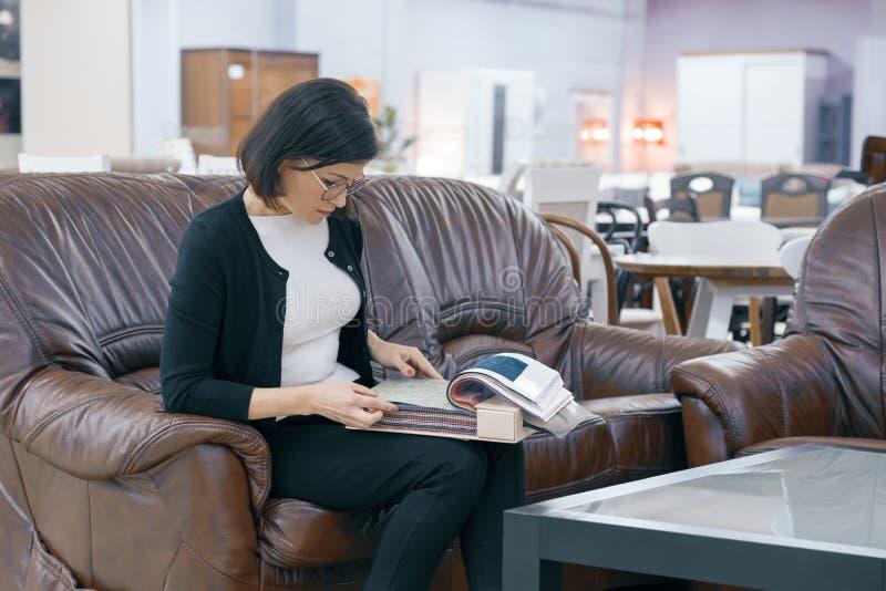 El comprador de mujer adulta que mira un libro con las telas de tapicería, hembra se está sentando en el sofá de cuero marrón en  foto de archivo