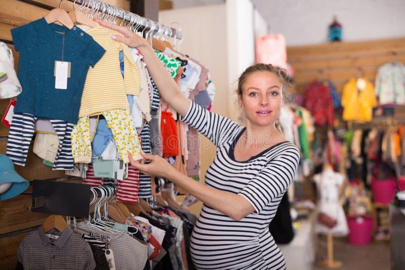 El comprador embarazada de la hembra revisa la ropa recién nacida en la tienda foto de archivo