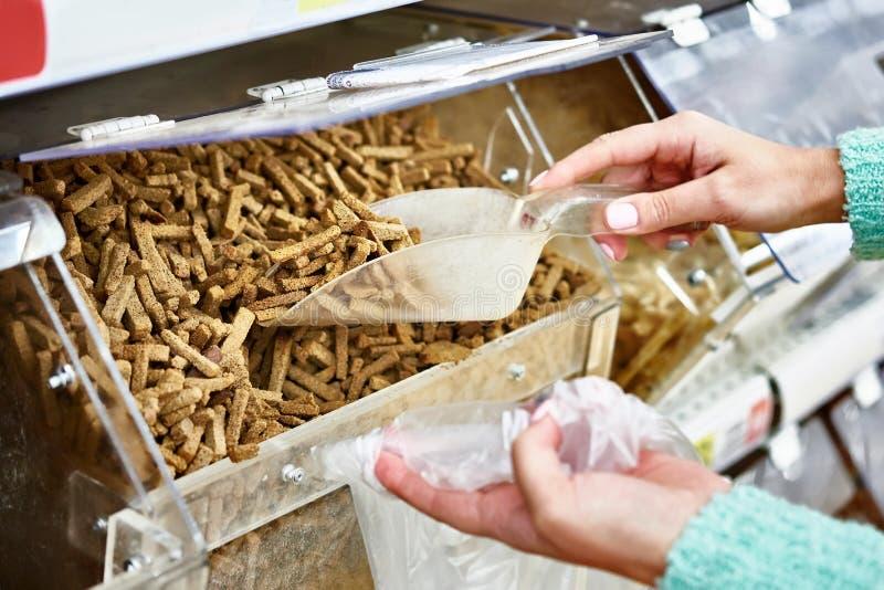 El comprador en tienda compra galletas del pan usando la cucharada para los productos fotos de archivo libres de regalías