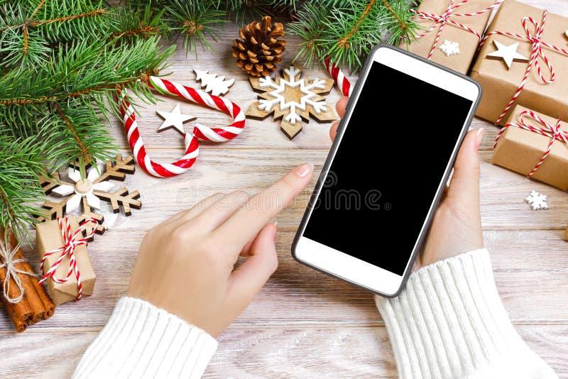 El comprador femenino hace orden en la pantalla del smartphone con el espacio de la copia Compras en línea de la Navidad Presente fotografía de archivo