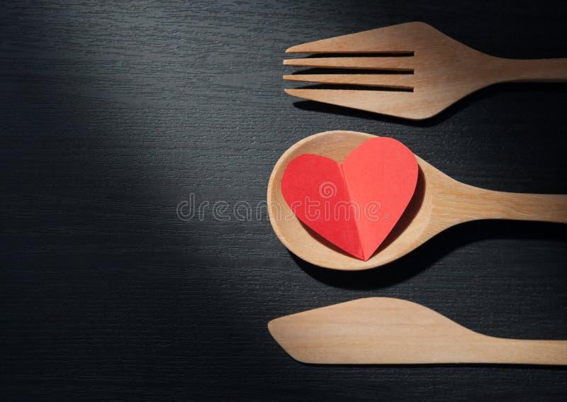 El concepto, corazón de A está en una cuchara, una bifurcación y un cuchillo de madera como alguno imagenes de archivo