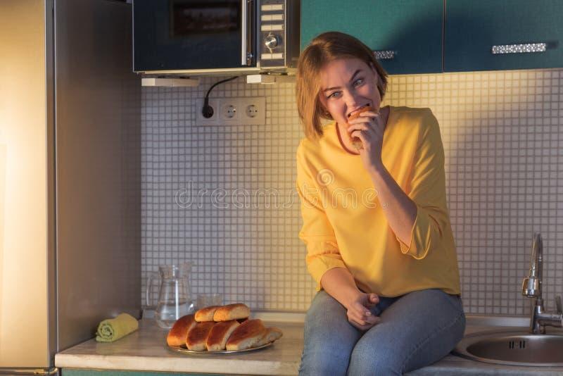 El concepto de abandonar dietas mujer joven codicioso que come la torta por la tarde que se sienta en la tabla en la cocina foto de archivo