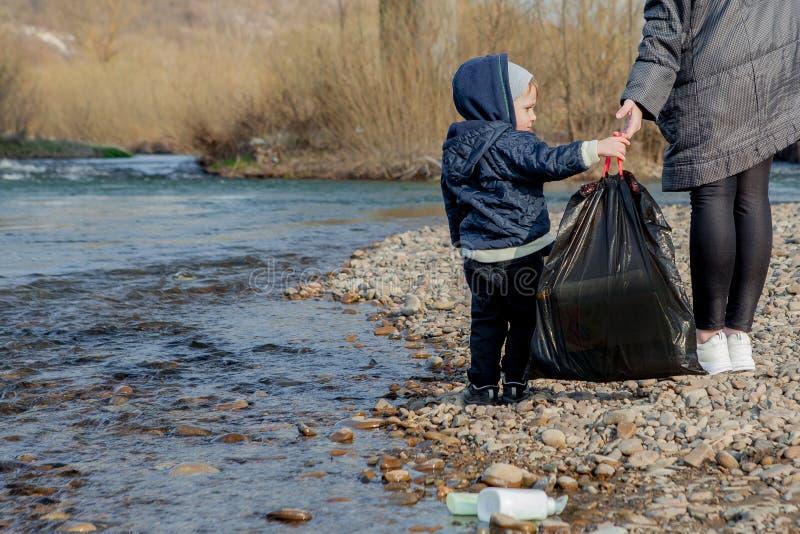El concepto de ahorro del ambiente, un niño pequeño y su madre está recogiendo la basura y las botellas plásticas en la playa foto de archivo libre de regalías