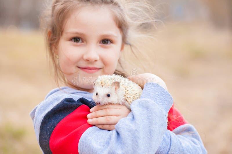 El concepto de alegr?a Muchacha que sostiene un erizo El peque?o jugar del beb? imagenes de archivo