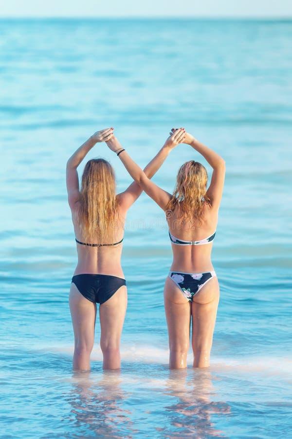 El concepto de amistad femenina muchachas que llevan a cabo las manos cruzadas imagen de archivo