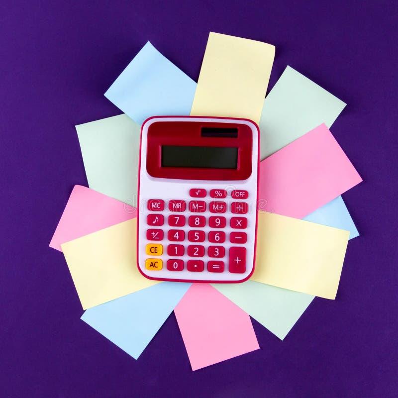 El concepto de análisis, analytics, cálculos La calculadora miente en las hojas de papel coloreadas fotos de archivo