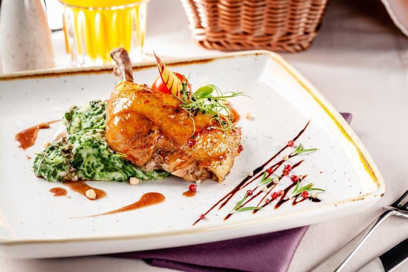 El concepto de cena en un restaurante japonés Guarnición de la espinaca con crema y piernas de pollo esmaltadas en una salsa pica fotografía de archivo libre de regalías