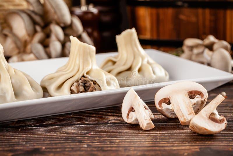 El concepto de cocina georgiana Khinkali de la pasta blanca con las setas Platos de porción en el restaurante georgiano en una pl imagen de archivo libre de regalías