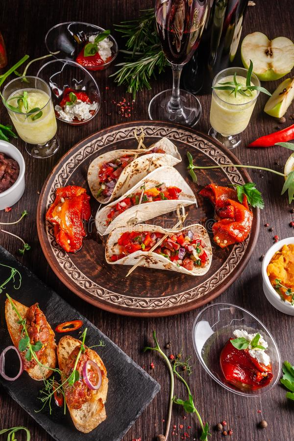 El concepto de cocina mexicana Comida y bocados mexicanos en una tabla de madera Taco, sorbete, tártaro, vidrio y botella de vino imagen de archivo libre de regalías