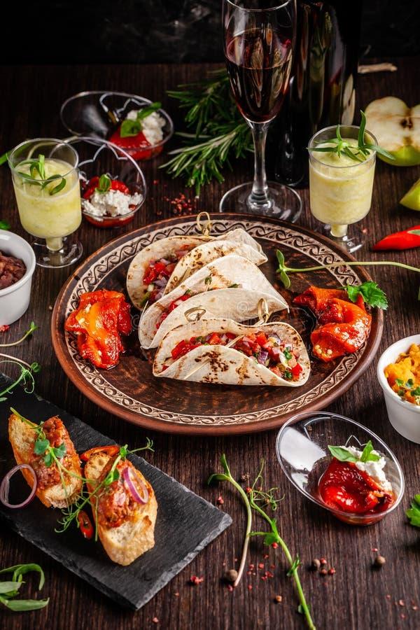 El concepto de cocina mexicana Comida y bocados mexicanos en una tabla de madera Taco, sorbete, tártaro, vidrio y botella de vino imágenes de archivo libres de regalías