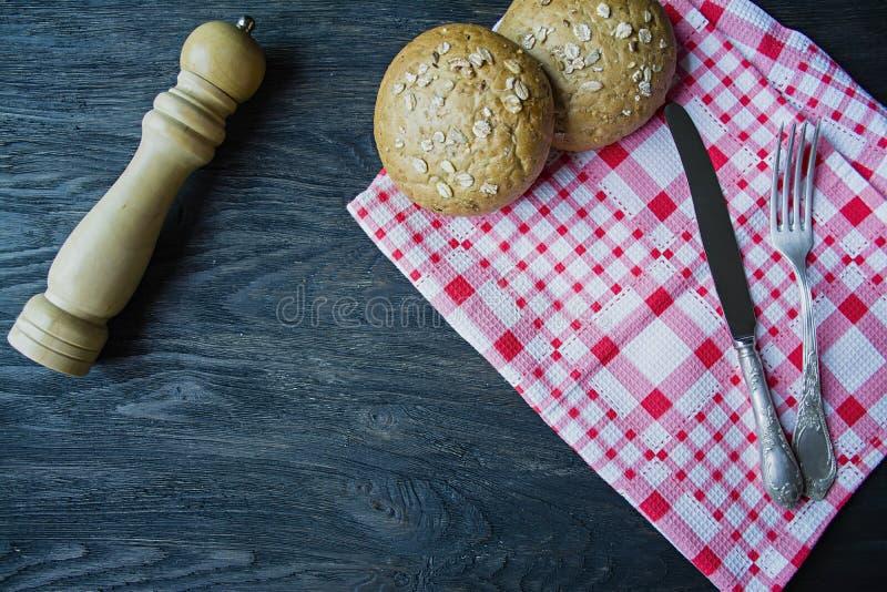 El concepto de cocinar Bifurcaci?n, cuchillo de la comida, servilleta a cuadros, bollos con las semillas de girasol, coctelera de imagenes de archivo