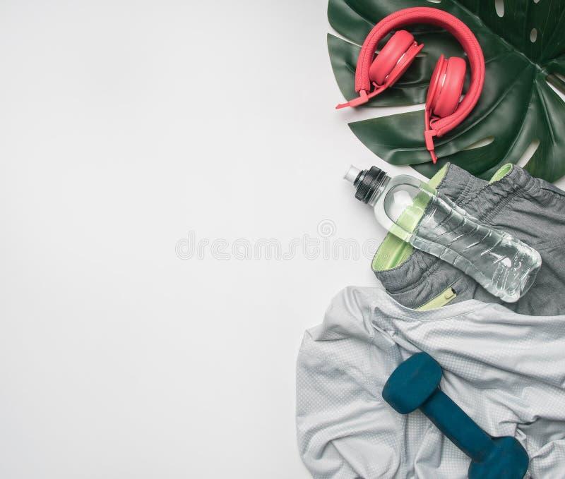 El concepto de deportes forma de vida, ropa de deportes y accesorios se alineó en un fondo blanco, con la botella de agua y de ho imagen de archivo