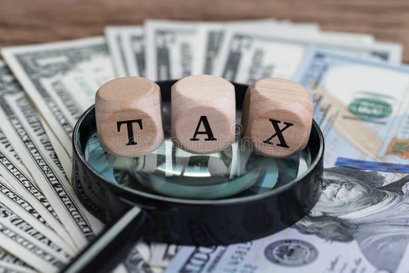 El concepto de dinero de impuestos personal, cubica el bloque de madera con la palabra IMPUESTO encendido fotos de archivo libres de regalías