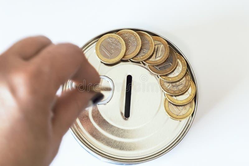 El concepto de dinero Una hucha bajo la forma de cuentas de una lata y, al lado de la hucha, de dinero y monedas se presenta fotografía de archivo libre de regalías