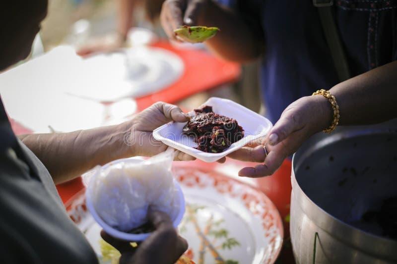 El concepto de distribución social: Gente pobre que recibe la comida de donaciones: Ayudan al vagabundo con el alivio de comida,  foto de archivo libre de regalías