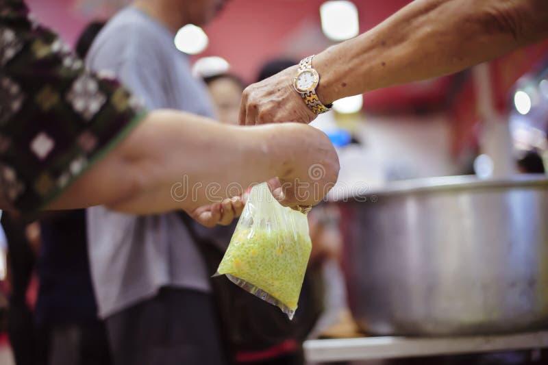 El concepto de donar la comida a los pobres para recibir la comida de las manos de los que son ricos foto de archivo libre de regalías