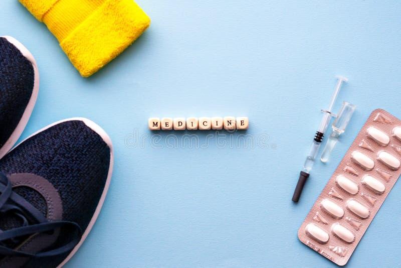 el concepto de doping en deporte Medicina de la inscripción en un fondo azul Zapatos de los deportes, píldoras, jeringuilla con l imagen de archivo libre de regalías