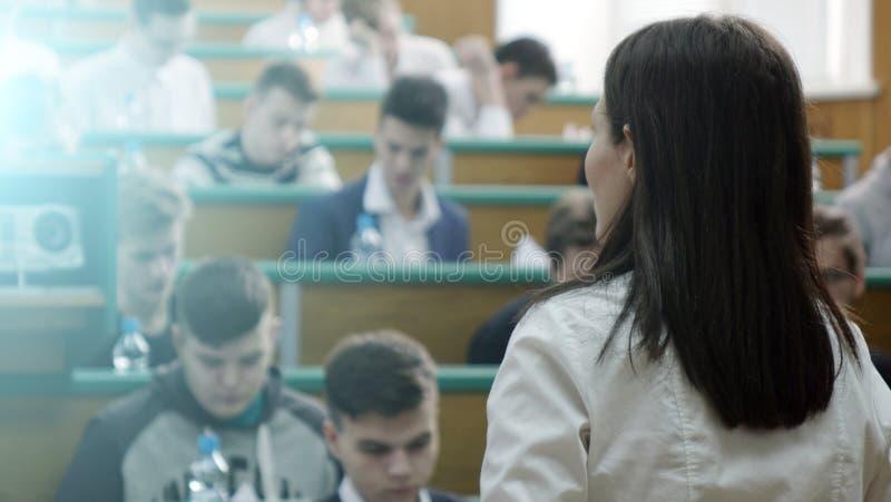 El concepto de educación está en estudiantes borrosos en la sala de clase con los profesores imágenes de archivo libres de regalías
