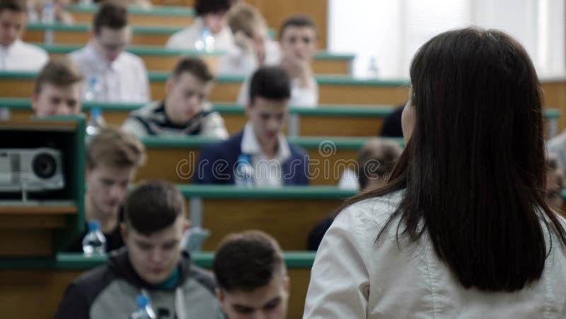 El concepto de educación está en estudiantes borrosos en la sala de clase con los profesores imagen de archivo libre de regalías