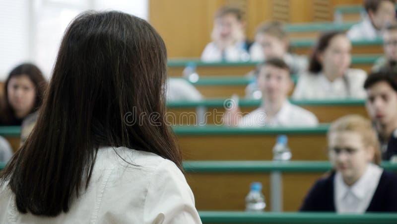 El concepto de educación está en estudiantes borrosos en la sala de clase con los profesores foto de archivo