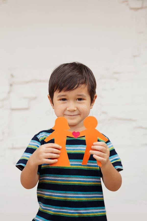 El concepto de familia con el niño pequeño que soportaba la cadena de papel formó como un par tradicional con el corazón imagen de archivo