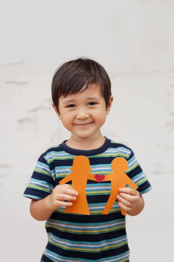 El concepto de familia con el niño pequeño que soportaba la cadena de papel formó como un par tradicional con el corazón imagenes de archivo