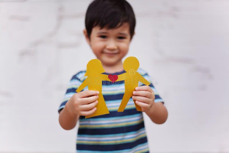 El concepto de familia con el niño pequeño que soportaba la cadena de papel formó como un par tradicional con el corazón fotos de archivo libres de regalías