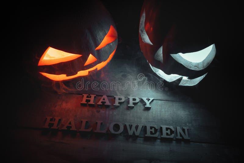 El concepto de Halloween dos que brillan intensamente angr ligero anaranjado y azul fotos de archivo