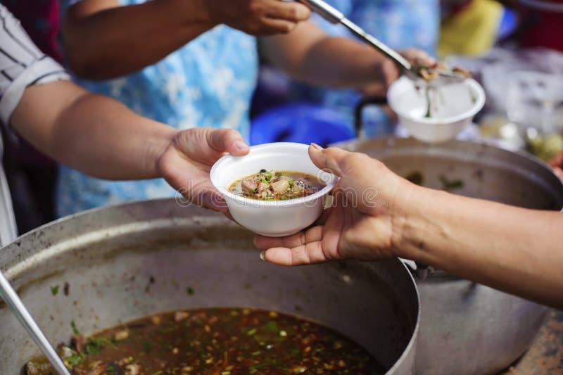 El concepto de humanitarismo: Las manos de refugiados han sido ayudadas por la comida de la caridad para aliviar hambre: Concepto fotografía de archivo libre de regalías