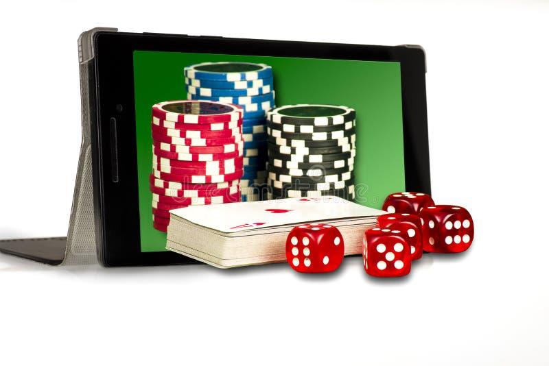 El concepto de juego en línea, de dados, de microprocesadores, y de tarjetas en el fondo de la tableta fotografía de archivo libre de regalías