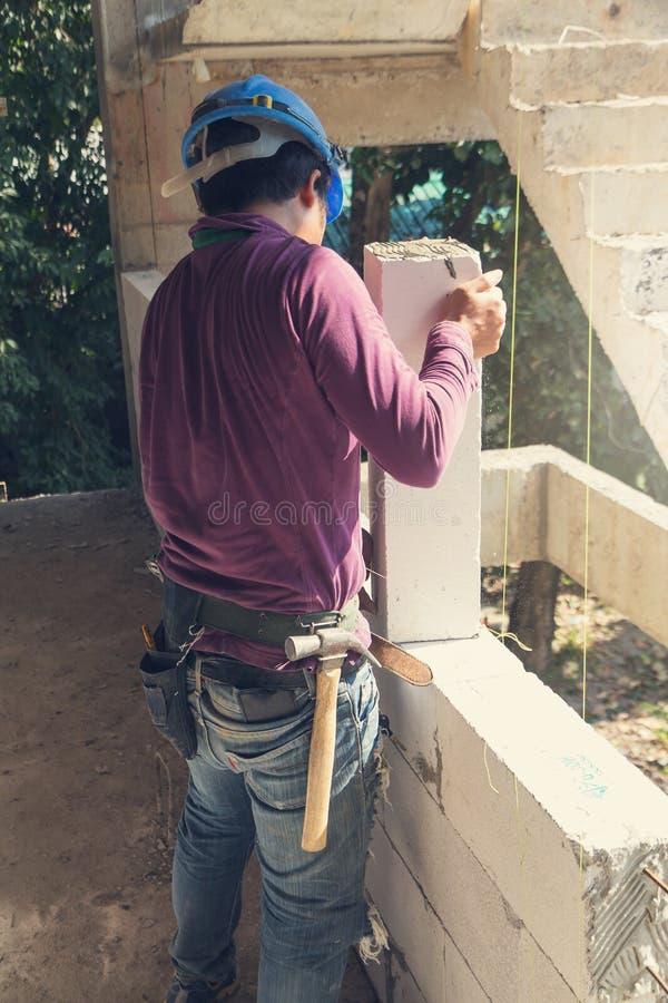 El concepto de la construcción, trabajador del albañil que instala el wite bloquea t fotos de archivo libres de regalías