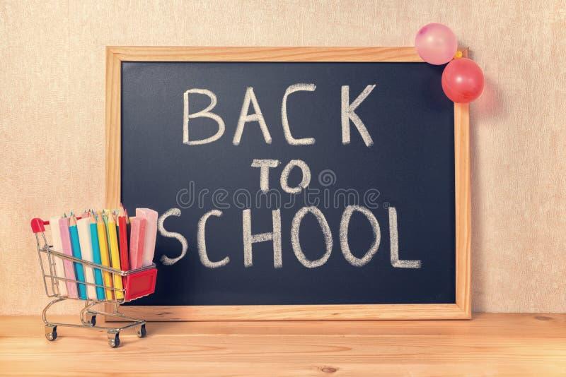 El concepto de la educación con el texto de nuevo a escuela se escribe en chalkbo imagen de archivo libre de regalías