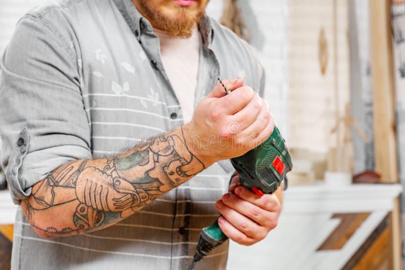 El concepto de la profesión, de la carpintería, de la artesanía en madera y de la gente, carpintero prepara el taladro para el tr imagen de archivo