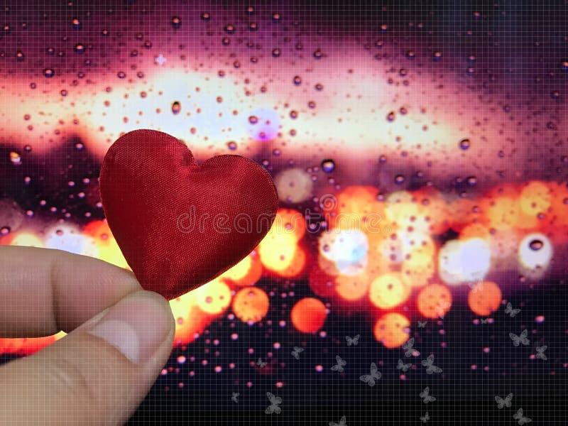 El concepto de la tarjeta del día de San Valentín, el corazón con el bokeh y el descenso llueven el fondo fotografía de archivo libre de regalías