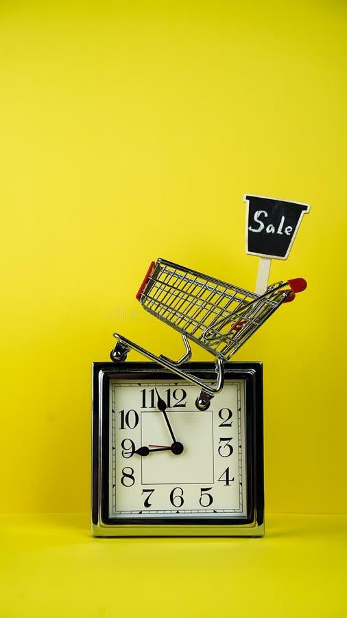 El concepto de la venta de la Navidad y de Black Friday platea el reloj, carretilla de la tienda del carro de la compra con venta imagen de archivo