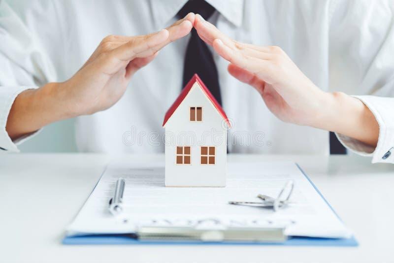El concepto de protecti de Insurance Home del agente de venta de la casa en propiedad fotografía de archivo libre de regalías