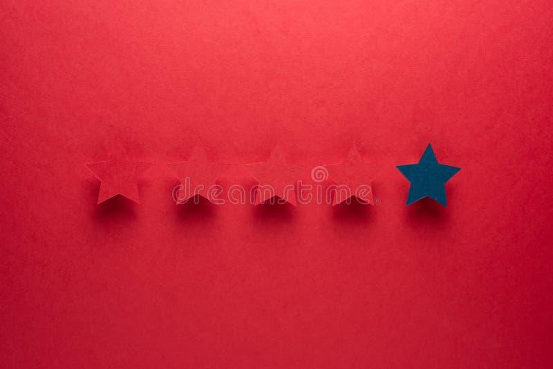 El concepto de reacción o de excelencia es diferente todo el mundo, sea el primer la estrella azul se destaca contra el rojo fotos de archivo libres de regalías